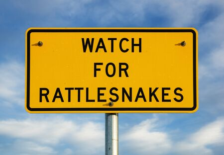 watch for rattlesnakes sign with partly cloudy blue sky background