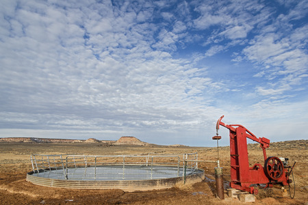 water well and pump filling a frozen over stock tank