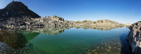 panorama of a still clear mountain lake with rocks on the bottom and reflection Stock Photo