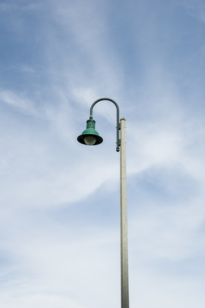 streetlight: green bent down streetlamp with partly cloudy sky background