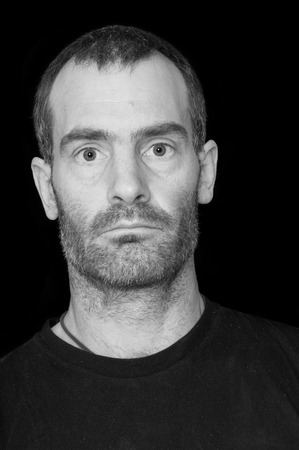 grizzled: black and white portrait of a rugged grizzled middle aged man with black t-shirt on black background Stock Photo