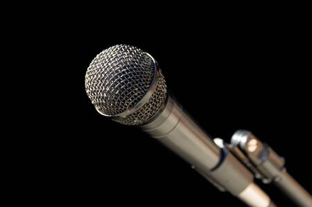 silver gray microphone on a stand with a black background Stock Photo