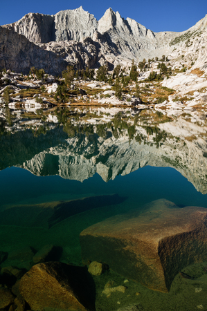 sierras: Mount Cotter reflected in a clear lake in the Sixty Lakes Basin of Kings Canyon National Park California Stock Photo