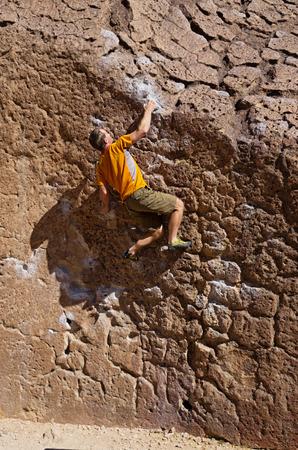 bouldering: un uomo bouldering sui pianori vulcanici vicino a Bishop California