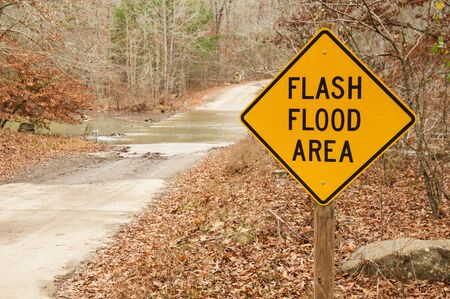 flash flood area sign with stream crossing behind it