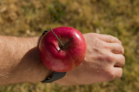 a joke redneck apple watch made out of a red apple strapped to a wrist