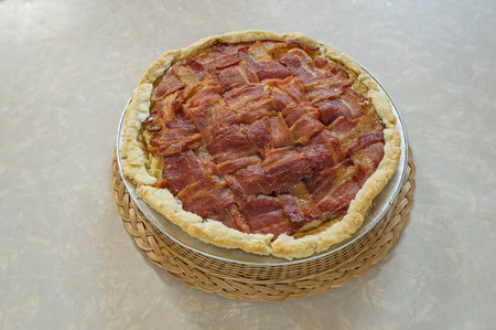 home made bacon lattice top mashed potato pie sitting on table on a wicker hot pad Stock Photo