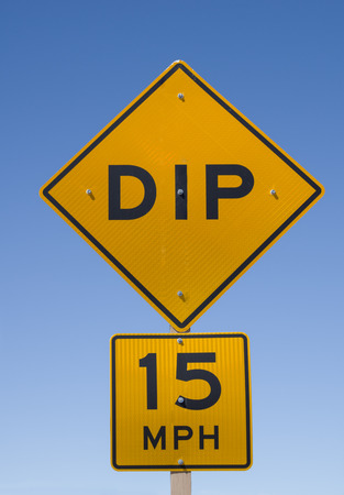 15: dip 15 mph road sign with blue sky background