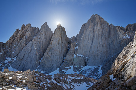 the sun slips behind Keeler Needle next to Mount Whitney and Day Needle or Crooks Peak in the high Sierra Nevada Mountains