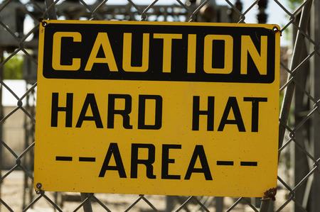 yellow and black caution hard hat area sign wired to a chain link fence Stok Fotoğraf