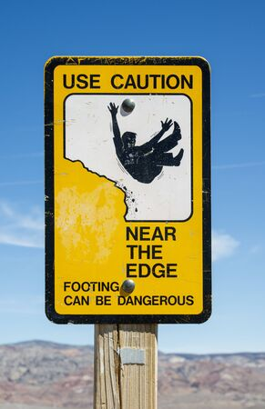 steep cliff sign: use caution near the edge warning sign at overlook Stock Photo