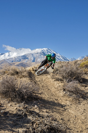 mountain biker: a mountain biker leans into a turn in the desert foothills with mountain in the background and copy space