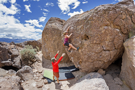 a couple bouldering at the Happy Boulders with the woman climbing and the man spotting