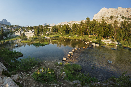 john muir trail: stepping stones on a trail across a stream in the Sierra Nevada Mountains