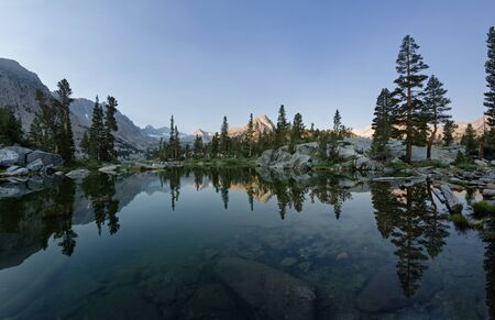 john muir wilderness: reflection of the mountains and trees in blue lake in the morning Stock Photo