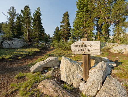 wooden trail sign: sign pointing to the hiker trail and the stock trail in the Sierra Nevada Mountains Stock Photo