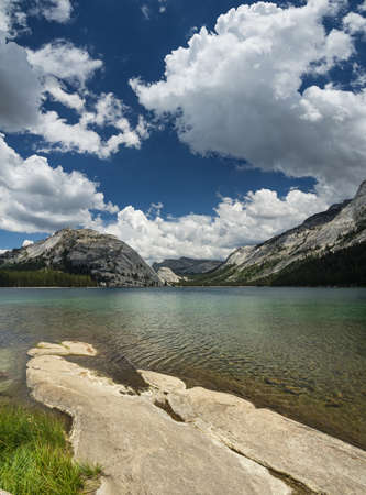 Tenaya Lake in the Yosemite National Park high country with foreground rock slab and white clouds in the sky