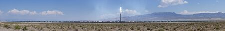 panorama of the Crescent Dunes concentrated thermal solar power plant with mirrors reflecting sunlight onto the central tower and into the sky