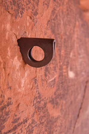drilled: old rusty iron piton hammered into a drilled hole in red sandstone
