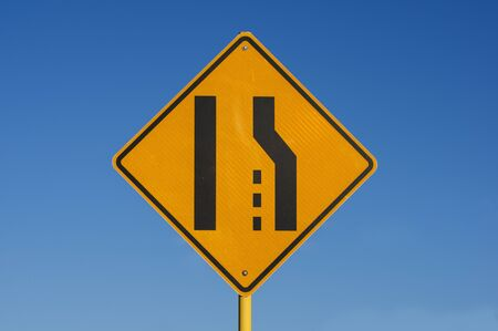 yellow and black right lane ends sign with blue sky background Stock Photo