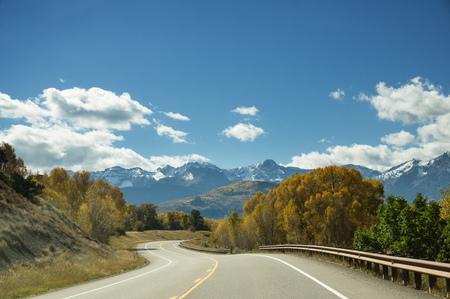 a winding mountain road goes between yellow aspen trees towards distant mountains Stock Photo