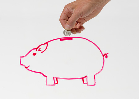 a mans hand putting a coin into a drawing of a piggy bank in pink on a whiteboard Stock Photo