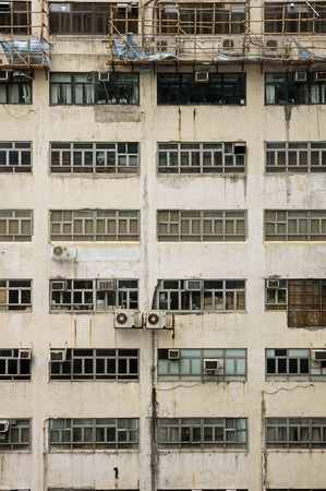 dingy building side with windows window air conditioning units scaffolding and grime from Hong Kong