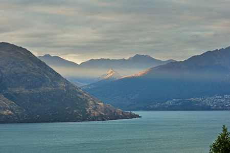 a sunray comes under the clouds and hits a distant peak above Lake Wakatipu and Queenstown New Zealand Stock Photo