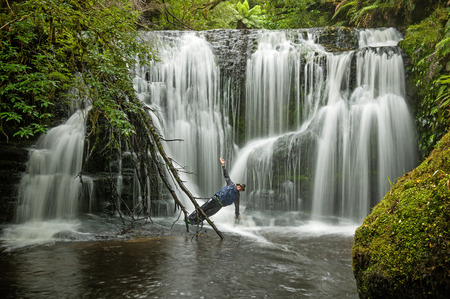 long exposure of man doing yoga pose side plank in a waterfall Stock Photo