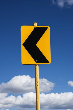 sign with black arrow pointing left warning of a curving road with blue sky and clouds background