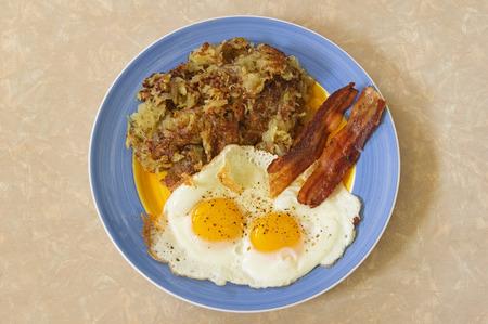 ハッシュの朝食プレート ブラウンズ 2 つの卵とベーコン