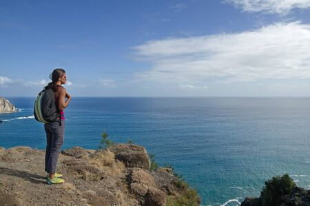 overlook: woman looks out over the Pacific Ocean from Makapuu Point on Oahu Hawaii Stock Photo