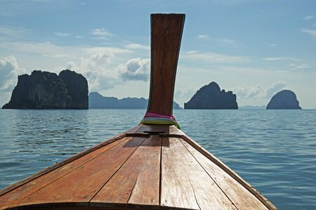 prow: longtail boat prow in Thailand in the Andaman Sea with islands off the bow