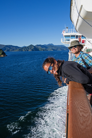couple on New Zealand Ferry look over the side in Queen Charlotte Sound