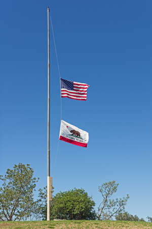 US and California flags flying at half mast on a hill top with blue sky background