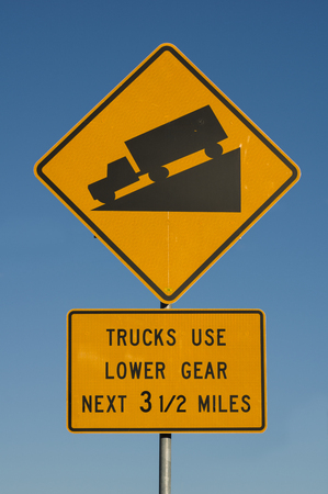 downgrade: steep hill trucks use lower gear road sign with blue sky background