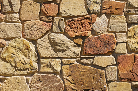 tan and reddish stone wall background texture Banco de Imagens