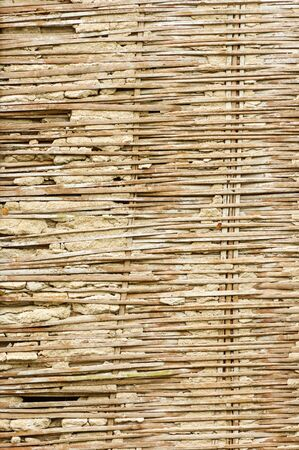 old broken bamboo lath and plaster wall in rural Thailand Stock Photo