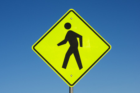 yellow and black pedestrian crossing road sign with blue sky background