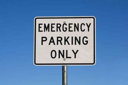 white and black emergency parking only road sign with blue sky background