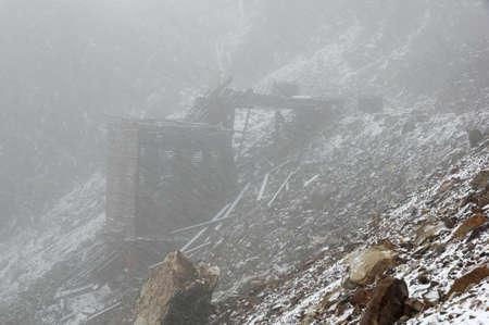 Old Adamson Mine Ruins in a summer Sierra snowstorm Stock Photo