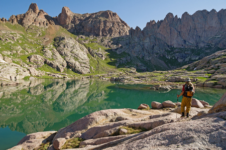 a hiker looks at the reflection in one of the Twin Lakes near Chicago Basin in the San Juan Range of Colorado Stock Photo