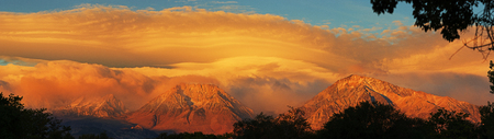 lenticular cloud: a storm clears at sunrise over the Eastern Sierra Nevada Mountains including Mount Tom and Basin Mountain from Bishop California