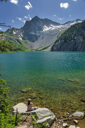 woman sits on a rock on the shore of Snowmass Lake in Colorado Stock Photo