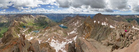 panorama from the summit of Sunlight Peak in the San Juan Mountains of Colorado with two hikers