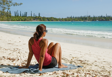 a woman sits on a tropical beach on Isle Of Pines in New Caledonia