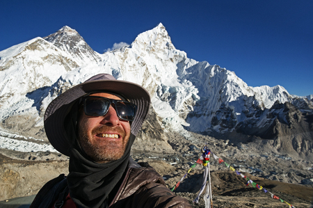 man in a selfie with Mount Everest in the background taken from the summit of Kala Patthar