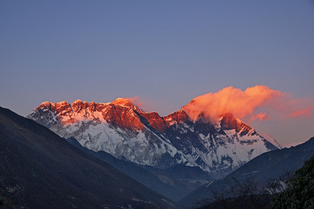 mount everest: last light on Mount Everest Nuptse and Lhotse with a few clouds viewed from Tengboche Stock Photo