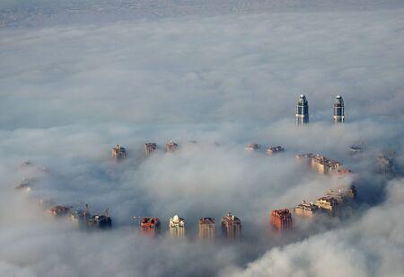 Altos edificios suben por encima de la niebla del suelo visto desde arriba en Doha, Qatar Foto de archivo