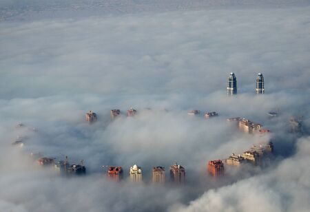 tall buildings rise above ground fog as viewed from above in Doha, Qatar Stock Photo